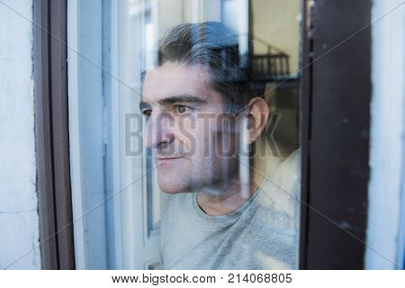 close up portrait of sad and depressed 40s man looking through window glass reflection lonesome and thoughtful suffering depression thinking and feeling low in life crisis and problem concept