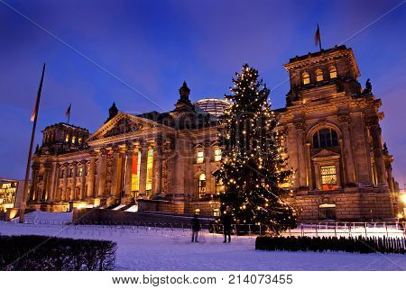 Reichsatag Building In Winter With Christmas Tree And Snow In Berlin