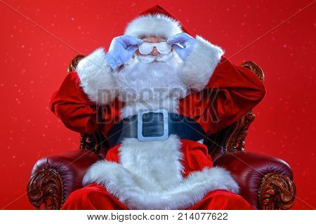 Cool modern Santa Claus in  snowy glasses  sitting in his armchair. Red background. Christmas concept.
