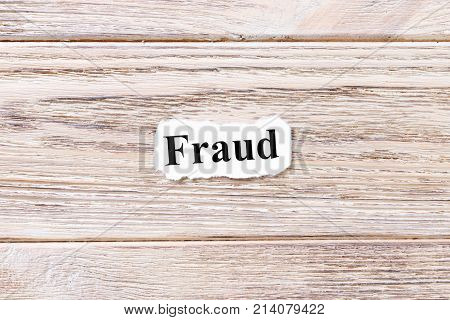 fraud of the word on paper. concept. Words of fraud on a wooden background.