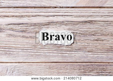 BRAVO of the word on paper. concept. Words of BRAVO on a wooden background.