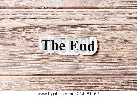 The End of the word on paper. concept. Words of The End on a wooden background.