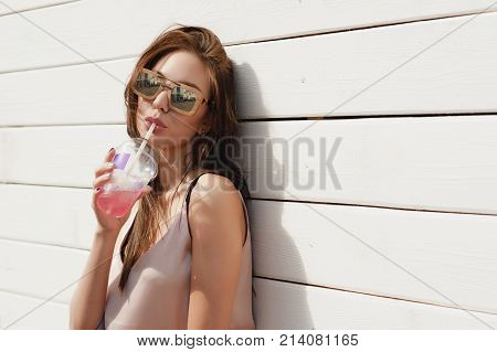 Portrait Of A Beautiful Lady In Sunglasses, In A Wooden Frame. Dressed In A Stylish Beige Blouse, Bl