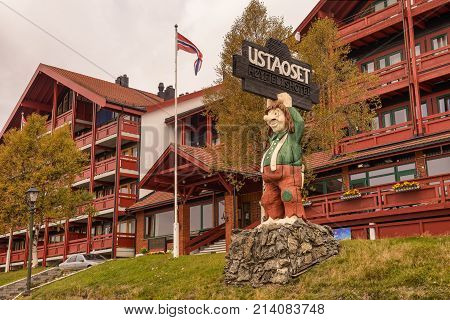 USTAOSET, NORWAY - SEPTEMBER 25, 2014 : Ustaoset Resort at the Ustevatn lake in the municipality of Hol, Buskerud county, Norway. Large wooden troll statue is placed in front of it.