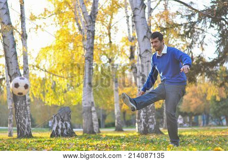 Young businessman kick the ball in park. Man in a blue sweater kicking ball