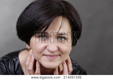Portrait of a woman aged on a gray background. A woman after fifty. Portrait of a beautiful young woman aged. Ordinary woman