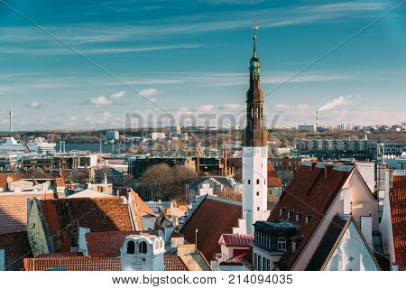 Tallinn, Estonia. Tower Of Church Of Holy Ghost Or Holy Spirit Is Medieval Lutheran Church Located Behind Raekoja Plats, Opposite Great Guild And Maiasmokk And Roofs Of Other Houses In Winter Day.