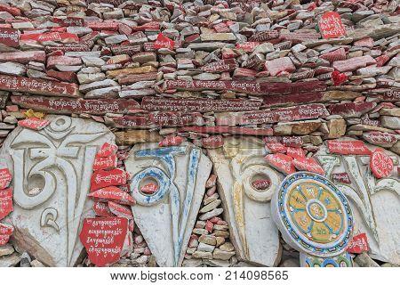 Yushu, China - November 3, 2017: Mani Stones Wall At The Mani Temple (mani Shicheng) Wall With Buddh