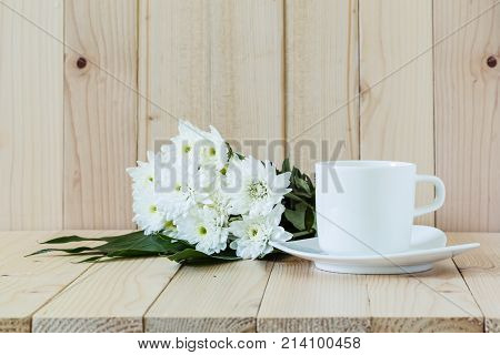 White Chrysanthemum Flowers With Coffee Cup On Wooden Background