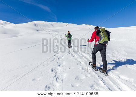 Mature couple hiking with snowshoes in winter mountain landscape. Alps, Germany, Bavaria, Allgau.