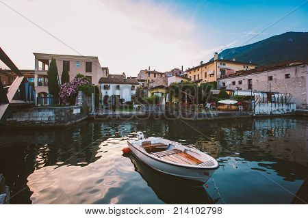 Sunset On The Lake Lago Di Garda On The Coast Of Salo Boat Near The Pier On The Background Of The Ol