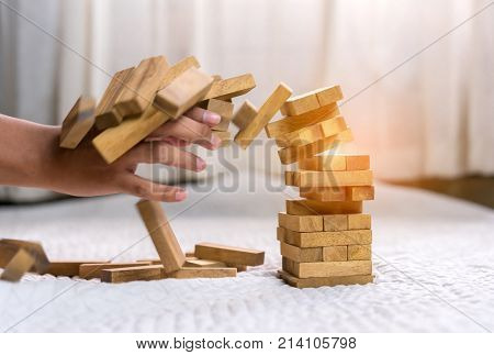 Young man pulling out wood block fail on building tower at home and drape change choice business risking dangerous project plan failure construction