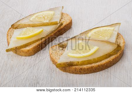 Two Sandwiches With Smoked Halibut And Lemon On Table