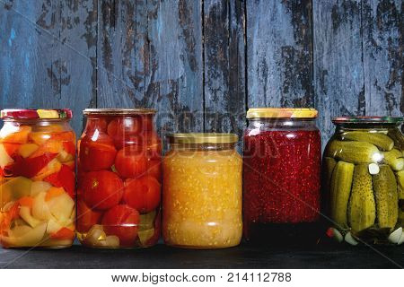 Variety glass jars of homemade pickled or fermented vegetables and jams in row with old dark blue wooden plank background. Seasonal preserves.