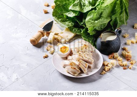 Ingredients for cooking classic Caesar salad. Sliced baked chicken breast, green roman salad, parmesan cheese, boiled egg, croutons, salt, jug of sauce over gray texture background. Copy space.