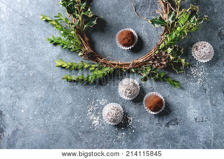 Variety of homemade dark chocolate truffles with cocoa powder, coconut, walnuts as Christmas gift with decorative Christmas wreath over blue texture background. Top view, copy space.