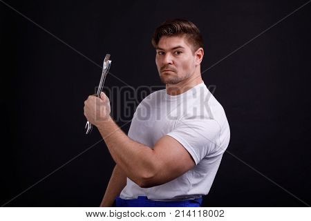 Worker inflated in a white T-shirt holding a wrench on a black background