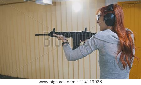 Woman shooting with a Mashin gun in shooting gallery, close up