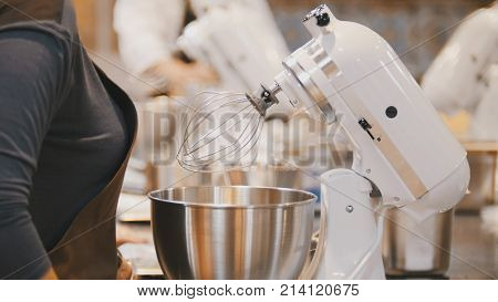 Woman on the kitchen near electric mixer ready for cooking, close up