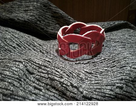 Bracelet faux red leather on brown and grey background