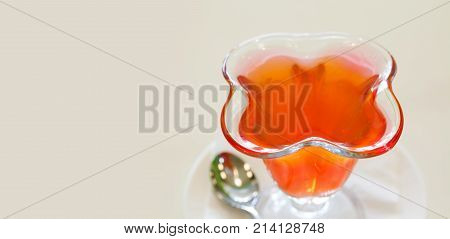 Red Jelly in glass plate, fruit gelatin dessert beige background. soft focus. copy space. Beautiful dessert menu template.