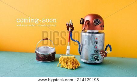 Web site under construction Coming Soon template page. Robot washer with mop and bucket of water, orange wall green floor interior.