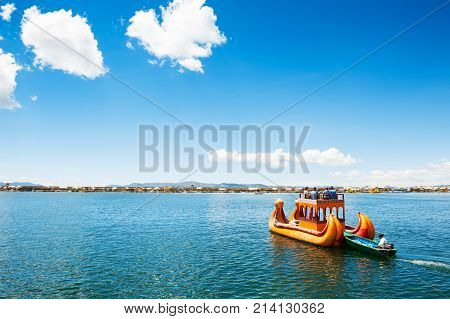 Titicaca lake Puno Peru - March 20 2017. Traditional Totora boat with tourists near Uros floating islands on Titicaca lake in Puno Peru South America