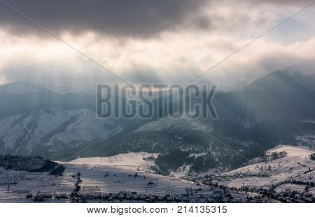 Sunbeams Through Clouds Over The Snowy Mountains
