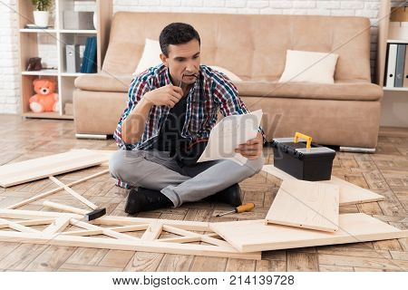 The young man tries himself to fold his bookcase. He reads the instructions. He uses tools for furniture. He will use this furniture for the interior of his room.