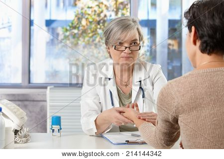 Happy mature female doctor sitting at desk in doctor's room taking pulse of patient, smiling.