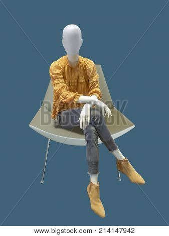 Female mannequin sitting on armchair over blue background. No brand names or copyright objects.