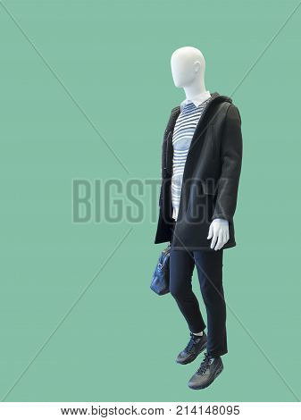 Full-length male mannequin dressed in warm coat with hood isolated on green background. No brand names or copyright objects.