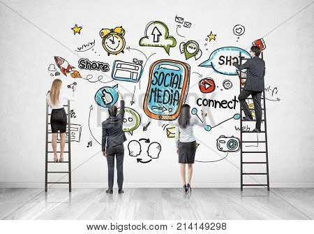 Rear view of members of a business team. Some are standing on ladders some on the floor drawing a social media sketch on a concrete wall in a room with a wooden floor.