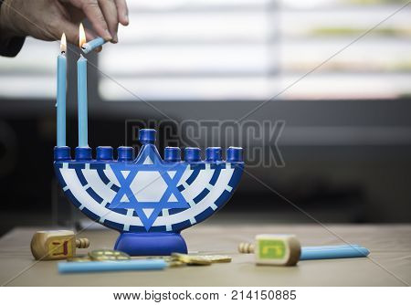 Hanukkah candles lit for the holiday celebration surrounded by dreidels and chocolate coins