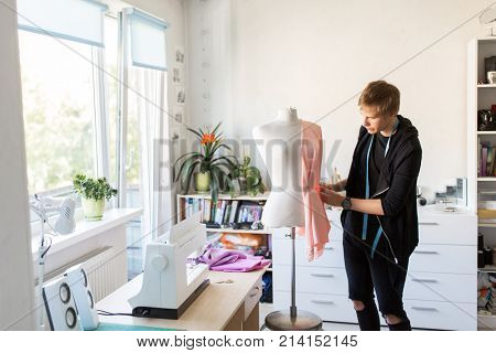 people, clothing and tailoring concept - fashion designer with dummy, cloth and pins making new dress at studio