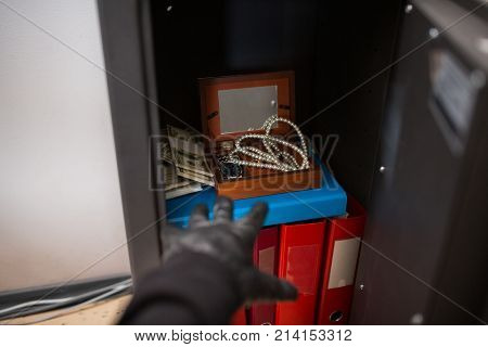 poster of theft, burglary and people concept - thief stealing valuables from safe at crime scene