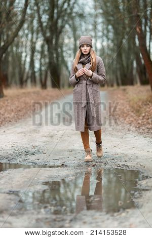 Girl In A Knitted Hat And Scarf At A Puddle In The Fall On Nature.
