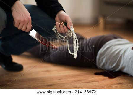 murder, robbery and people concept - criminal or murderer holding knife in blood and jewelry and dead woman body lying on floor at crime scene