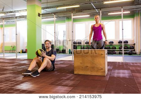 fitness, sport, training, exercising and people concept - man and woman with medicine ball ready to do curl ups and box jumps in gym