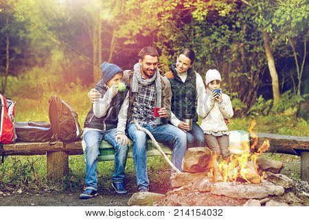 camping, travel, tourism and people concept - happy family sitting on bench and drinking hot tea from cups at camp fire in autumn forest