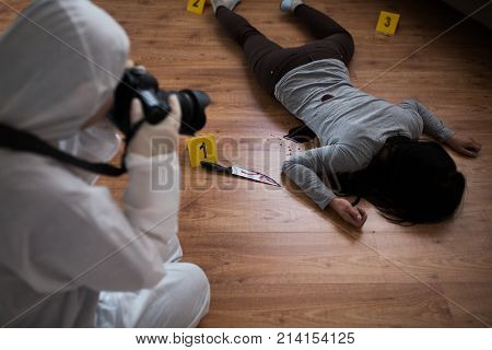 murder, investigation, forensic examination and people concept - criminalist with camera photographing dead female victim body at crime scene