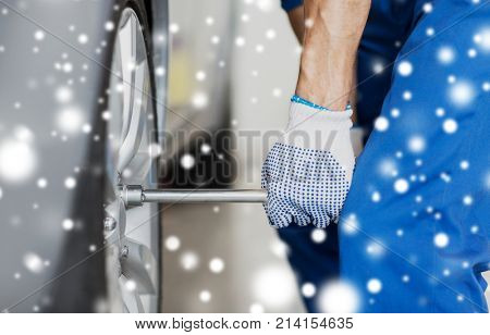 car service, repair, maintenance and people concept - auto mechanic hands with electric screwdriver changing tire at workshop over snow