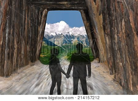 Road to a brighter future for a young couple. Two transparent silhouettes of people looking at a mountain landscape from a dark tunnel.