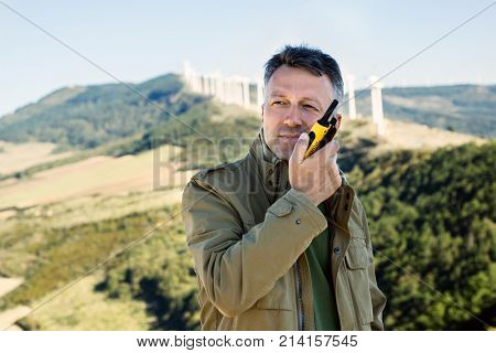 Man talking with portable radio transmitter outdoor over the wind turbines, image toned.