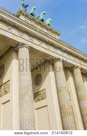 Low point of view image neo-classical architectural columns and bronze statue four horses looking down on top of the Brandenburg Gate