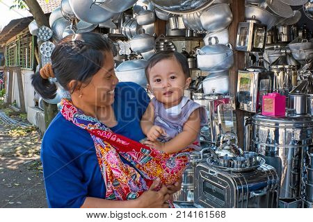 JAVA, INDONESIA - DECEMBER 21, 2016: Mother and child doing shopping in front of a kitchen utensils shop on Java, Indonesia, 21st december 2016
