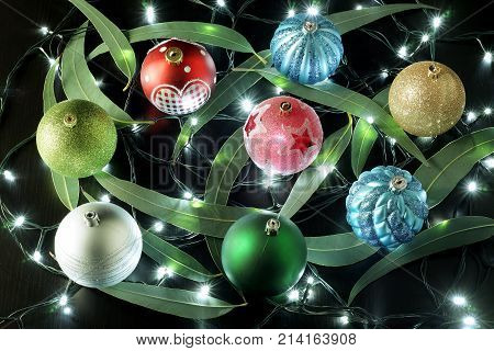 Christmas Baubles and Gum Tree Leaves on Black Background