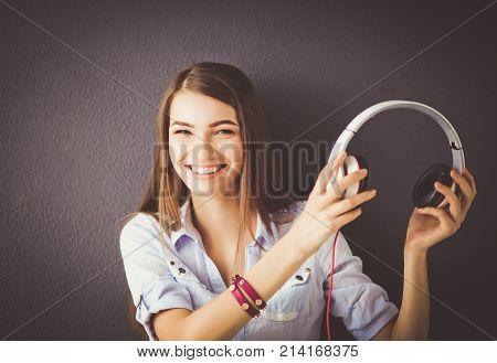 Woman listening music in headphones on windowsill background.
