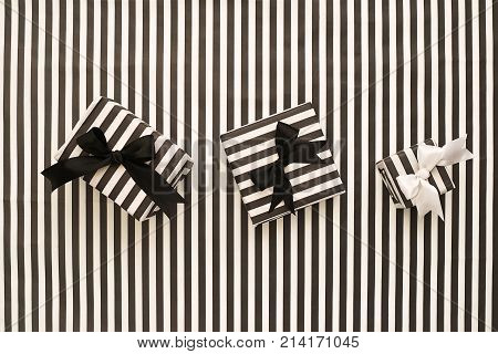 Striped black and white gift boxes on a striped background. The concept for greeting cards, invitations. Top view.