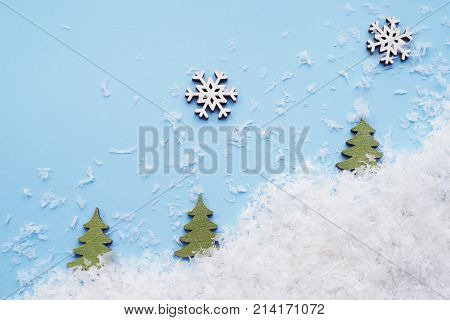 Small snowflakes and Christmas trees on a laconic blue background. A template for late postcards, calendars. Top view.